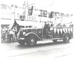 1938 International Harvester Pumper in a parade in front of Two Legs Inc. 1003 South Clinton...