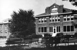 Allen County Infirmary, Fort Wayne IN: front view with men sitting on benches in the foreground.