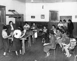African-American girls playing table tennis and reading at Wheatley Center, 1936.